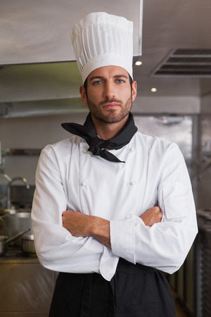 Serious head chef looking at camera with arms crossed in a commercial kitchen photo