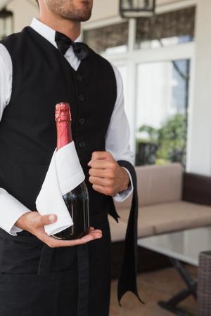 magnum: Gar�on tenant magnum de champagne dans le patio du restaurant de