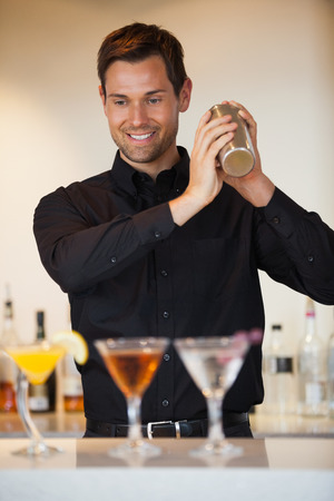 Happy bartender shaking cocktails at the bar photo
