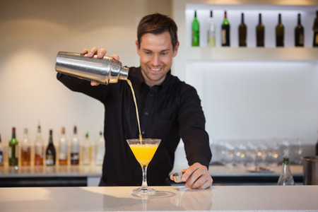Glimlachend barman gieten gele cocktail in glas aan de bar Stockfoto