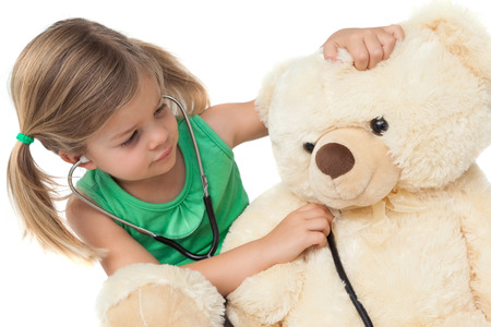 Cute little girl playing doctor with her teddy bear on white background photo