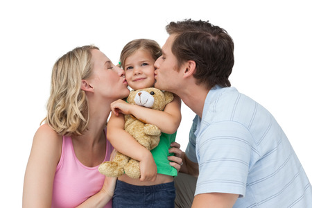 Parents kissing their little girl on her cheeks on white background photo