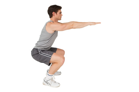 Fit man doing squats on white background Stock Photo