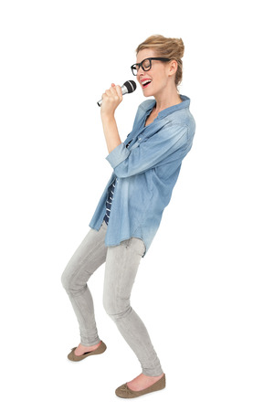 over white background: Beautiful young woman singing into a microphone over white background