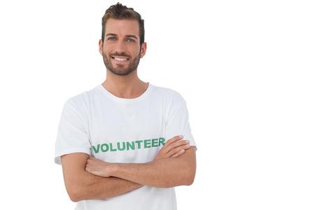 mani incrociate: Ritratto di un volontario maschio felice in piedi con le mani incrociate su sfondo bianco