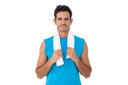 Portrait of a fit young man with towel standing over white background photo