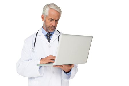 Concentrated male doctor using laptop over white background photo