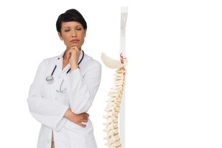 Thoughtful female doctor with skeleton model over white background photo