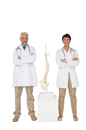 Portrait of two smiling doctors with skeleton model over white background photo