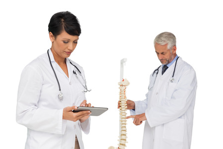 Portrait of  female doctor holding digital table with colleague by skeleton model over white background photo