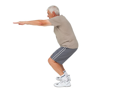 Full length side view of a senior man stretching hands over white background photo