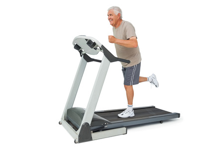 Full length of a senior man running on a treadmill over white background photo