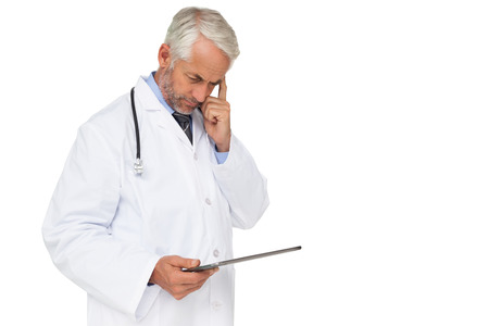 Concentrated male doctor using digital tablet over white background photo