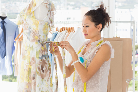 Side view of a beautiful female fashion designer working on dress at the studio photo