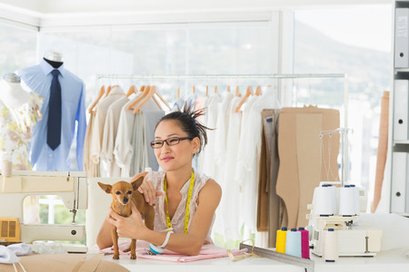 Portrait of a beautiful female fashion designer with chihuahua in the store photo