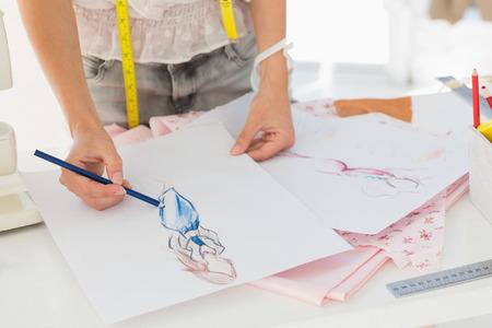 Close-up medio sectie van een vrouwelijke mode-ontwerper werken op haar ontwerpen in de studio Stockfoto