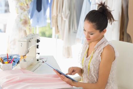 Side view of a young female fashion designer using digital tablet in the studio Stock Photo - 27142598