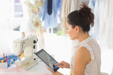 Side view of a young female fashion designer using digital tablet in the studio Stock Photo - 27142600