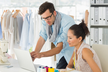 Male and female fashion designers using laptop at work in a studio