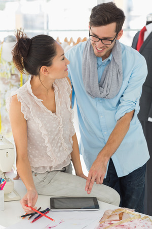 Male and female fashion designers using digital tablet in a studio photo