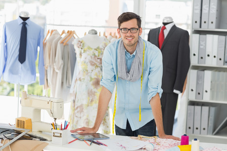 Portrait of a smiling handsome male fashion designer standing in the studio photo