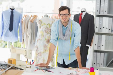 robo: Retrato de un apuesto joven diseñador de moda masculina de pie sonriente en el estudio Foto de archivo