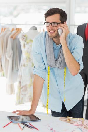 robo: Sonriendo apuesto hombre de diseñador de moda masculina con teléfono móvil en el estudio