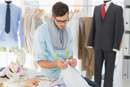 male fashion: Concentrated young male fashion designer at work in a studio Stock Photo