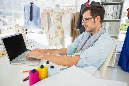 Side view of a concentrated young male fashion designer using laptop in the studio photo