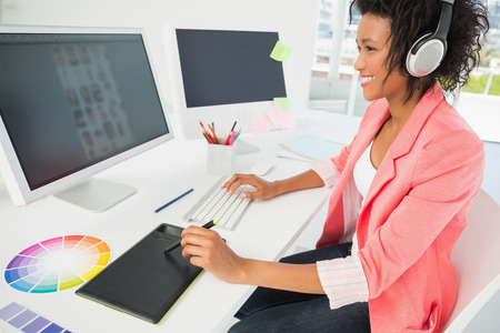 Side view of a casual female photo editor using computer in a bright office photo