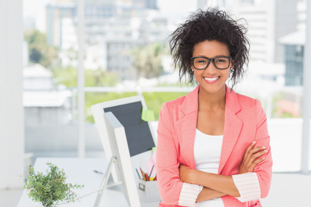 african american woman business: Portrait of a casual female artist standing with arms crossed at a bright office