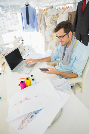 Side view of a young male fashion designer using laptop and cellphone in the studio photo