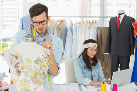 Male and female fashion designers at work in a studio photo