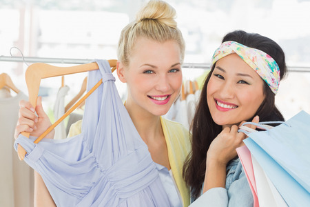 Portrait of two happy young women shopping in clothes store photo