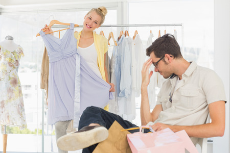 bored man: Bored man sitting with shopping bags while woman selecting dress in the background
