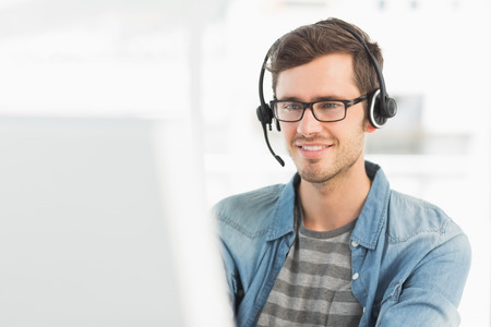 Sourire jeune homme décontracté avec un casque en utilisant l'ordinateur dans un bureau lumineux