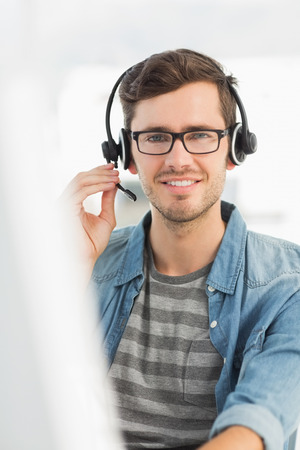 Portrait of a smiling casual young man with headset using computer in a bright office photo