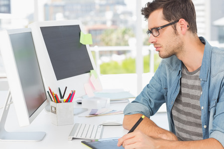 Side view of a casual male photo editor using graphics tablet in a bright office photo