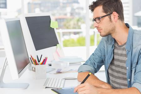 Vue de côté d'un éditeur de photos mâle occasionnel utilisant une tablette graphique dans un bureau lumineux Banque d'images - 28408013
