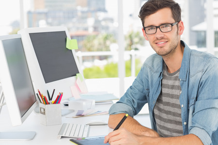 graphics tablet: Portrait of a casual male photo editor using graphics tablet in a bright office