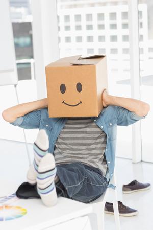 smiley content: Un jeune homme d�contract� avec la bo�te souriant heureux sur le visage alors qu'il �tait assis sur une chaise au bureau