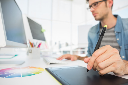 casuals: Side view of a casual male photo editor using graphics tablet in a bright office Stock Photo