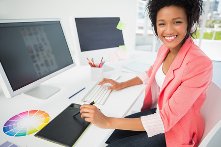 Portrait of a casual female photo editor using computer in a bright office photo
