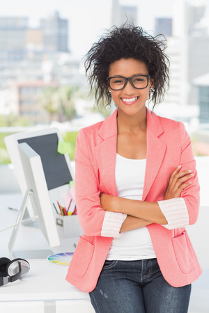 Portrait of a casual female artist standing with arms crossed at a bright office photo