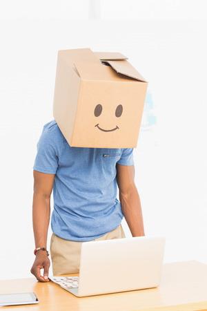 smiley content: Un jeune homme d�contract� avec la bo�te souriant heureux sur le visage en face de l'ordinateur portable au bureau