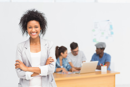 african american woman business: Portrait of a casual female artist with colleagues in the background at a bright office Stock Photo