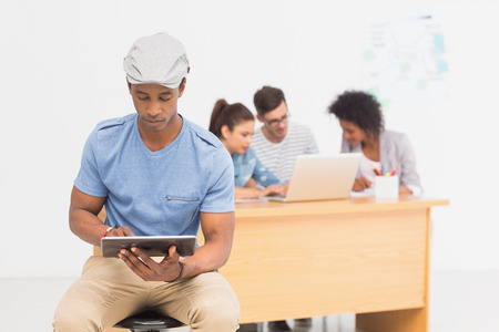 Casual male artist using digital tablet with colleagues in the background at a bright office photo
