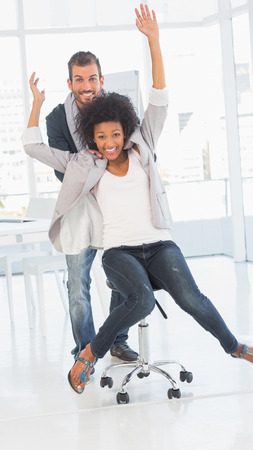 Portrait of playful happy young man pushing woman on chair in a bright office photo