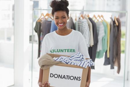 altruismo: Retrato de una mujer joven y sonriente con la donaci�n de ropa Foto de archivo