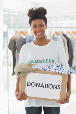 community outreach: Portrait of a smiling young woman with clothes donation